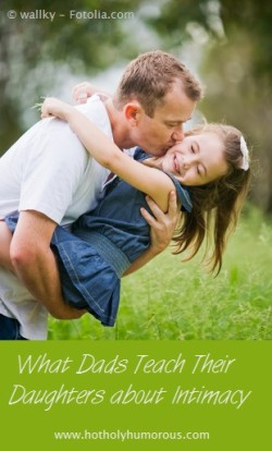 Dad holding & kissing daughter