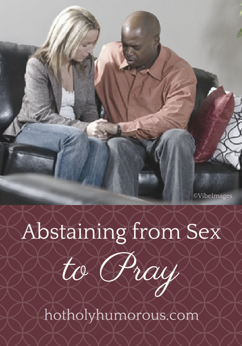 Couple sitting on a couch, holding hands, and praying together