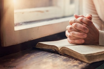 Woman's hands on Bible folded in prayer