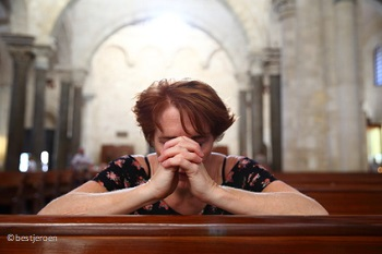 Woman praying in church sanctuary