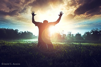 Person on knees praying at sunrise with hands lifted to Heaven