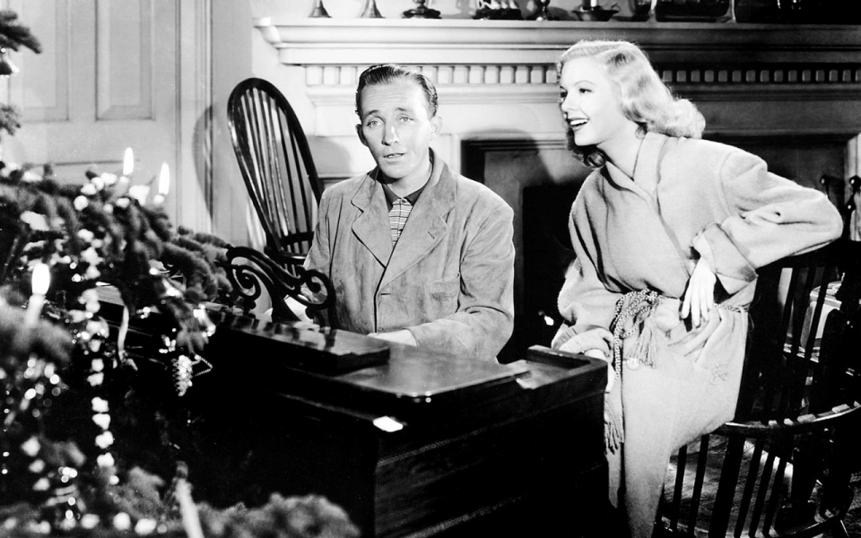 Hero playing piano and singing, while heroine sits nearby and sings along